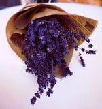 Naher hoher Blumenstrauß des Lavendels im braunen Papier gegen den weißen Hintergrund stockfotografie