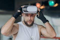 Naher hoher Boxer in den Kopfhörer-Trainingsdurchschlägen VR 360 im Kampf der virtuellen Realität lizenzfreie stockbilder