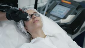 Naher hoher Cosmetologist macht Laser Gefäßabbau auf dem Gesicht der Frau mit spezieller Ausrüstung stock video