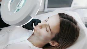 Naher hoher Cosmetologist mit Spritze macht Fraueneinspritzungen und -blicke durch kosmetisches Vergrößerungsglas stock footage