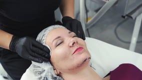 Naher hoher Cosmetologist s?ubert Frauenhaut mit nass Baumwollauflagen von der schwarzen Maske nach Laser-Schale stock video footage