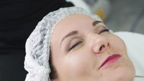 Naher hoher Cosmetologist s?ubert Frauenhaut mit nass Baumwollauflagen vor Gesichtssorgfaltverfahren stock video
