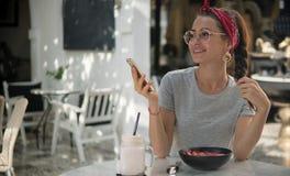 Naher hoher Schuss der hübschen jungen Frau im Straßencafé am Tisch, beiseite lächelnd stockbilder