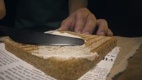 Naher hoher Schuss: der Koch verbreitet Butter durch Messer auf dem knusperigen gebratenen Toastbrot und macht das Sandwich, selb stock footage