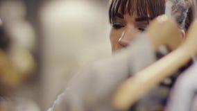 Naher hoher Schuss des attraktiven weiblichen Kundengesichtssuchens Kleidung auf einem Gestell in einem Bekleidungsgeschäft stock video