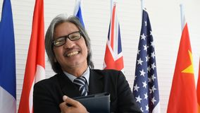 Naher hoher Schuss des Geschäfts oder des politischen Mannes lächelt und schaut vor internationalen Flaggen glücklich stock video