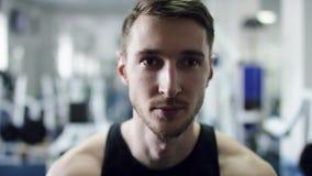 Naher hoher Schuss des Gesichtes eines jungen Atmungsmannes in einer Turnhalle stock video footage