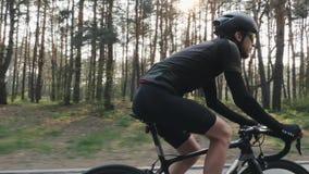 Naher hoher Schuss des radelnden Fahrrades des Radfahrers, das schwarzes Trikot, kurze Hosen, Sturzhelm und Sonnenbrille trägt Hi stock footage