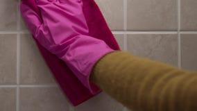 Naher hoher Schuss des Säuberns der Fliesenwand mit der Hand im Gummihandschuh durch Serviette, Werbung von Haushaltschemikalien, stock footage