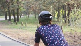 Naher hoher Schuss des weiblichen Radfahrenreitenfahrrades in einem Park, der schwarzen Sturzhelm und blaues Trikot tr?gt stock footage