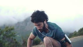 Naher hoher Schuss eines jungen kaukasischen männlichen Läufers, der seine Schuhe bindet und oben steht, betrachtend die Ansich stock footage