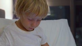 Naher hoher Schuss eines kleinen Jungen, der in seinem Bett nachts sitzt, spielt einen Tabletten-PC mit Schattenbildern eines Wol stock video footage