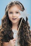 Naher hoher Schuss entzückender blauäugiger kleiner europäischer weiblicher Prinzessin hat langes gewelltes Haar, trägt Krone, hä stockbild