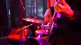 Naher hoher Schuss von den Männern, die weiße Bass-Gitarre auf Stadium nachts spielen stock video footage