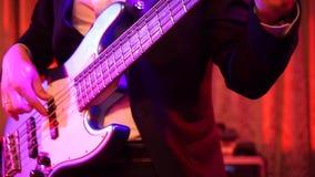 Naher hoher Schuss von den Männern, welche die weiße Bass-Gitarre mit 5 Schnüren auf Stadium nachts spielen stock footage