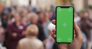 Naher hoher Schuss von den Mannhänden, die intelligentes Telefon mit grünem Schirm auf dem Stadtstraßenhintergrund halten Zwei in stock footage