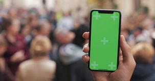 Naher hoher Schuss von den Mannhänden, die intelligentes Telefon mit grünem Schirm auf dem Stadtstraßenhintergrund halten Zwei in stock video