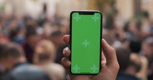 Naher hoher Schuss von den Mannhänden, die intelligentes Telefon mit grünem Schirm auf dem Stadtstraßenhintergrund halten Zwei in stock video footage