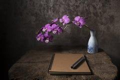 nahes Anmerkungsbuch und purpurrote Orchidee im Vase auf einem alten hölzernen tabl Lizenzfreie Stockbilder