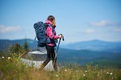 Nahes in den Bergen mit Rucksack- und Trekkingsstöcken morgens kampieren des Frauenwanderers lizenzfreie stockfotografie