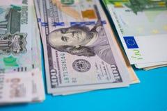 nahes hohes Bündel Geld Euros, Dollar, Rubel Banknoten auf dem blauen Hintergrund, Geschäft, Finanzierung, Einsparung, Konzept ei stockfotos