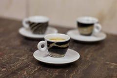 Nahes hohes Bild von drei kleinen Tassen und Untertassen, mit Kaffeeespresso, mit Tigermusterentwurf, auf Marmorhintergrund lizenzfreies stockbild