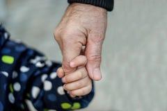 Nahes hohes Bild weniger Kleinkindkinderholdinghand eines älteren Verwandten: Großvater oder Urgroßvater lizenzfreies stockbild