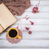 Nahes hohes der Kaffeetasse und des offenen Buches Winter- und Weihnachtszeitkonzept Stockfotos