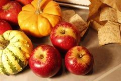 Nahes hohes Foto von dunkelroten Äpfeln und von Miniaturkürbisen stockfotografie