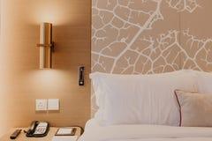 Nahes hohes Fragment des Schlafzimmers mit Leselampe im modernen Haus oder im Hotel stockbild