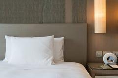 Nahes hohes Fragment des Schlafzimmers mit Leselampe und digitalem Wecker im modernen Haus oder im Hotel stockfotografie