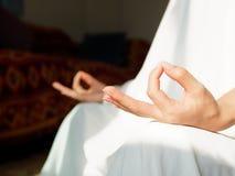 Nahes hohes Handzeichen der Frau in der weißen Robe, die Lotus Yoga Position, eine Tätigkeit tut, um physikalisch, geistlich und  stockbilder