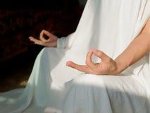 Nahes hohes Handzeichen der Frau in der weißen Robe, die Lotus Yoga Position, eine Tätigkeit tut, um physikalisch, geistlich und  lizenzfreies stockfoto