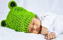 Nahes hohes Hauptfoto eines netten glücklichen schauenden entzückenden neugeborenen Babys mit grüner Kappe lizenzfreies stockbild