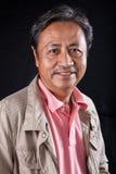 Nahes hohes lächelndes Glückgesicht des Porträts des alten Asiaten der Jahre 59s Stockfotografie