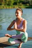 Nahes hohes Porträt der attraktiven Frau in meditierender Position auf hölzernem Klotz am See Junges Mädchen, das Yoga tut stockfotos