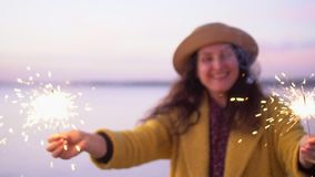 Nahes hohes Porträt der hübschen smilling Frau mit Wunderkerzen in den Händen schließen oben Funken zerstreut in verschiedene Ric stock video footage