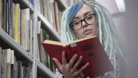 Nahes hohes Portr?t der Hippie-Frau rotes Buch in der Bibliothek lesend stock footage