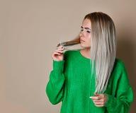Nahes hohes Porträt der jungen Frau beunruhigt über ihr Haar stockfotografie