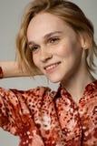 Nahes hohes Porträt der jungen Frau mit dem gelockten blonden Haar, durchbohrend in der Nase stockfotografie