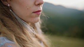 Nahes hohes Porträt der jungen Frau mit dem Haar, das im Wind betrachtet Sonnenuntergang im Berg durchbrennt Langsame Bewegung stock video