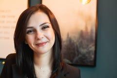 Nahes hohes Porträt der lächelnden jungen Geschäftsfrau, die Kamera betrachtet stockbild