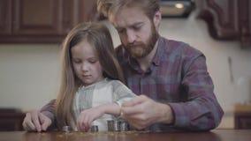 Nahes hohes Porträt des bärtigen Mannes sitzend am Tisch in der Küche mit seiner Tochter, die Geld zählt Beardie herein stock footage