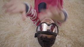 Nahes hohes Porträt des entzückenden Afroamerikanerjungen, der auf dem Boden auf dem beige flaumigen Teppich mit Skischutzbrill stock video