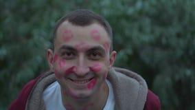 Nahes hohes Porträt des glücklichen jungen lächelnden Mannes mit Gesicht voll von Lippenstiftkennzeichen von Küssen stock video