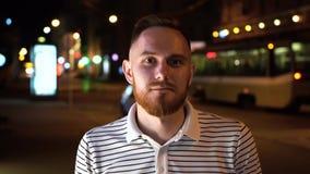 Nahes hohes Porträt des hübschen bärtigen Mannes in gestreiftem Polot-shirt auf Nachtstraße mit trammy auf dem Hintergrund stock video