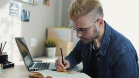 Nahes hohes Porträt des jungen attraktiven Mannes mit Gläsern und dem gelben Haar macht Anmerkungen auf Tagebuch Hauptfreiberufle stock video footage