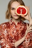 Nahes hohes Porträt des jungen blonden Mädchens im roten Hemd lizenzfreies stockfoto