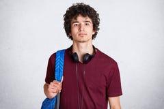 Nahes hohes Porträt des jungen Kerls mit dem gelockten Haar, tragende Kopfhörer, kastanienbraunes T-Shirt, hält blaues racksack,  lizenzfreie stockfotos