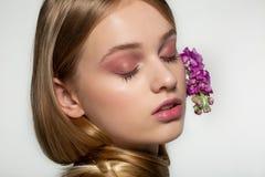 Nahes hohes Portr?t des jungen M?dchens mit geschlossenen Augen, helles Make-up, Hals eingewickelt im Haar, purpurrote Blumen gek lizenzfreie stockfotos